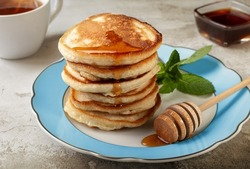 pancakes with honey on a light background. airy sweet pancakespancakes with honey on a light background. airy sweet pancakes