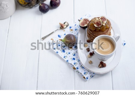 pancakes with jam and figs on a white plate and a cup of coffee on a white background #760629007