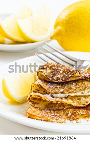 pancakes with lemons and sugar on white plate