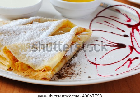 pancakes with powdered sugar. The dish is decorated by cowberry jam
