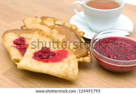 Pancakes with raspberry jam and a cup of tea on a wooden board