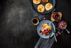 Pancakes with raspberry jam on a blue plate, frozen raspberries, a jar of raspberry jam, a cup of coffee, a frying pan with pancakes, fork and knife on dark metal table top view. Breakfast.