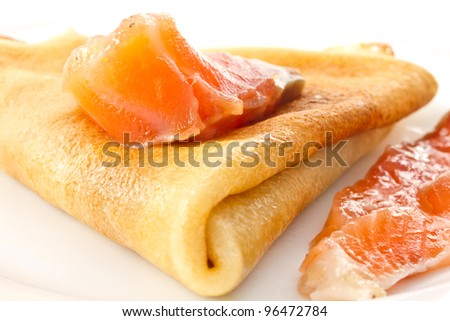 Pancakes with salted red fish on a white plate
