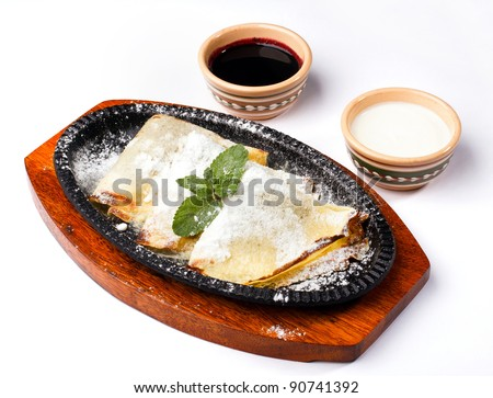 pancakes with sour cream and cherry jam on wooden kitchens tablet on a white background