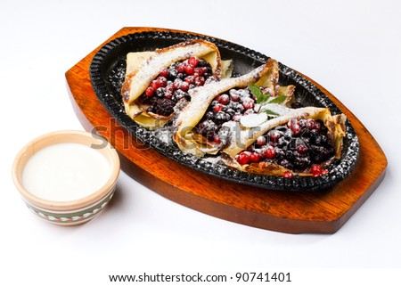 pancakes with sour cream and with berries on wooden kitchens tablet on a white background