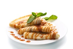 pancakes with syrup and mint on a white background