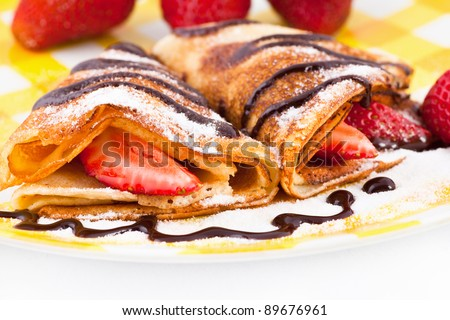 Pancakes with the strawberries on a plate, close-up