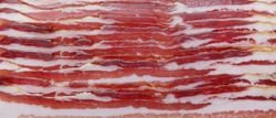 Pancetta. Close up of Italian pancetta cut into slices. Cured meat product. Food background. Panoramic macro image. Hi-res banner.