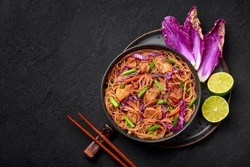 Pancit Bihon in black bowl on dark slate table top. Filipino cuisine noodles dish with pork belly, chicken, vegetables. Asian food. Top view. Copy space