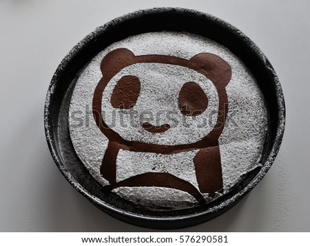 Panda made with sugar on a chocolate brownie cake in a round form
