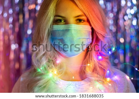 Pandemic Christmas. Covid-19 New Year party 2021. Winter holidays celebration hygiene. Portrait on blonde woman in protective face mask in rainbow neon lights on blur tinsel background.