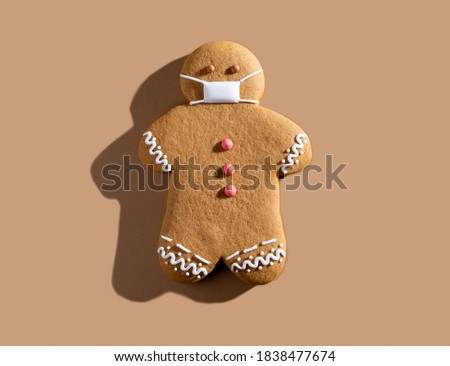 Pandemic Christmas. Quarantine celebration. Covid-19 winter holidays safety. New normal. Brown gingerbread man in protective face mask alone isolated on beige background.