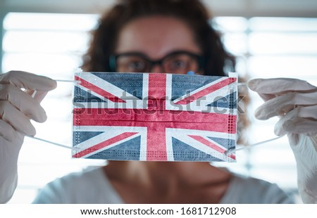 Pandemic Coronavirus. Close up of young woman with surgical mask with the UK flag on it. Concept of Coronavirus, COVID-19, health emergency and quarantine