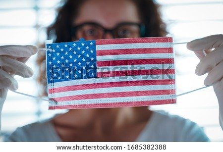 Pandemic Coronavirus. Close up of young woman with surgical mask with the USA flag on it. Concept of Coronavirus, COVID-19, health emergency and quarantine
