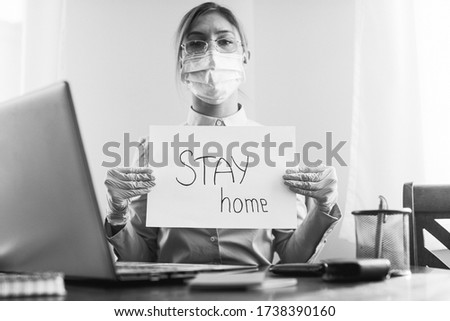 Pandemic Covid-19 Coronavirus. Stay Work at home, social distance. quarantined woman showing paper words stay home. Business concept. Working. Background. Mask. Stay home. Hope.