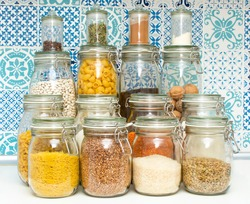Pandemic pantry with stocked food.  Emergency food prep during Coronavirus Covid-19 for survival. Supplies you need at home if you are quarantined. Prepping for quarantine - glass jars with provision.
