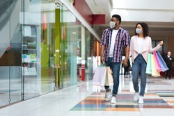 Pandemic Shopping. Black couple wearing protective face medical masks walking with shopper bags in mall, african american spouses making purchases during coronavirus quarantine, copy space