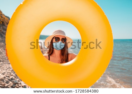 Pandemics, self-isolation, and vacations at sea. A young woman in a bathing suit and hat, with a medical mask on her face, looks through a hole in the swimming circle. Beach in the background