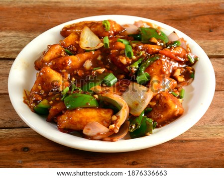 Paneer chilli is Indo Chinese cuisine dish, Paneer cubes tossed with tomatoes, onions, spring onions, chilli sauce. served over a rustic wooden background, selective focus Stock photo ©