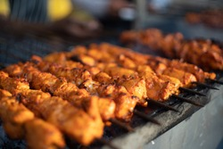 Paneer fish chicken tikka roasting on an open hearth with glowing coals and smoke coming out. A staple of indian cusine as a starter or with roti naan bread and a very spicy marination. North indians