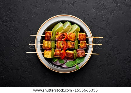 Paneer Tikka at skewers in black bowl at dark slate background. Paneer tikka is an indian cuisine dish with grilled paneer cheese with vegetables and spices. Indian food. Top view