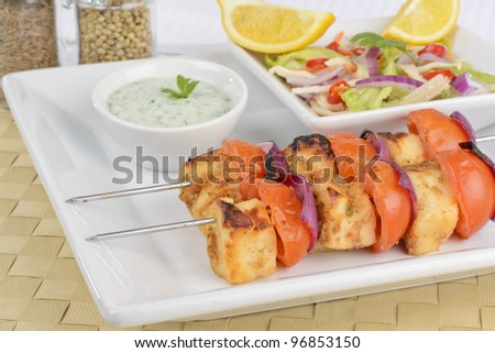 Paneer Tikka Kebab - Tadoori indian cheese skewers with tomato and red onions served with chrunchy, salad mint raita and lemon wedges.
