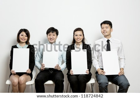 Panel of Business judges hold up blank score cards for your message.