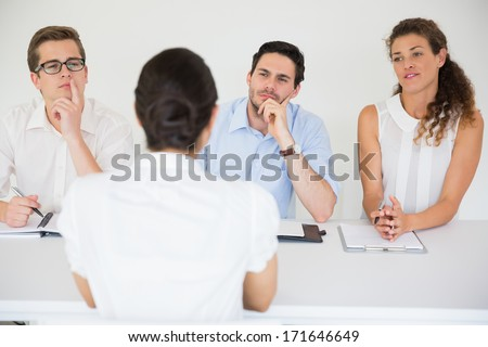 Panel of business people conducting job interview with female candidate