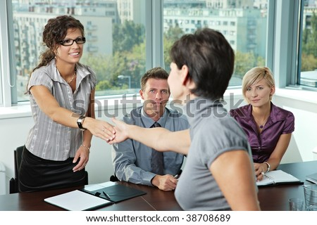Panel of business people sitting at table in meeting room conducting job interview greeting female applicant. - stock photo