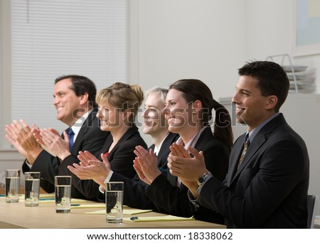 Panel of co-workers applauding