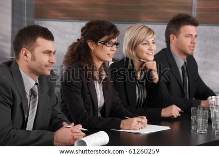 Panel of friendly businesspeople sitting at meeting table conducting job interview. ?