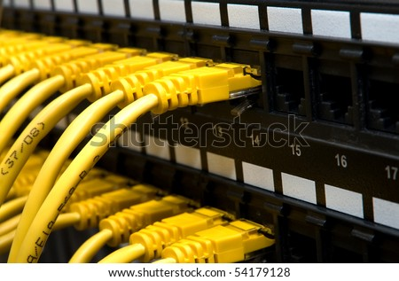 Panel of network switch with some yellow network cables