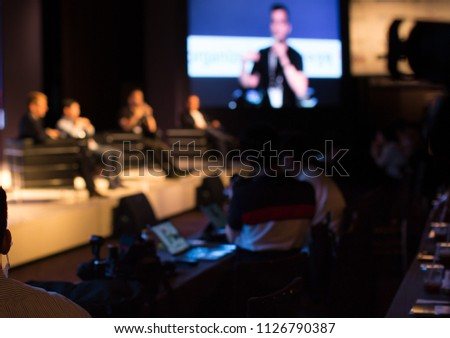 Panel Speaker on Stage Presenting Vision and Ideas. Conference Lecture Hall. Blurred De-focused Unidentifiable Presenter and Audience. People Attendees. Business Technology Event. Debate Discussion.
