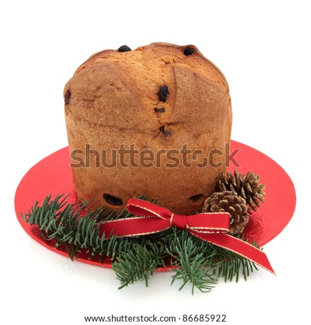 Panettone christmas cake with decorative red ribbon, pine cone and spruce fir leaf sprig isolated over white background.