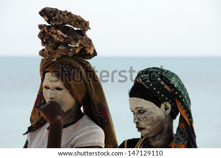 PANGANE, MOZAMBIQUE - AUGUST 27: Unidentified Makua woman, with traditional white face mask, welcomes a group of tourists, August 27, 2009 in Pangane, Mozambique  - stock photo