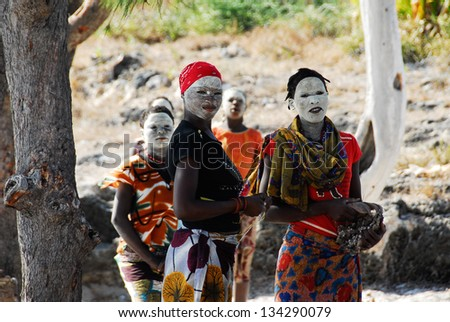 PANGANE, MOZAMBIQUE - AUGUST 27: Unidentified Makua women, with traditional white face mask, welcome a group of tourists, August 27, 2009 in Pangane, Mozambique