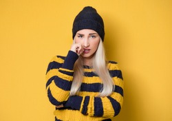 Panicked young woman biting fingernail, being terrible accident, model wearing woolen cap and sweater, isolated on yellow background. Frightened girl. Studio shot
