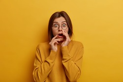 Panicking shocked European woman feels disappointed and impressed, hears something unbelievable, wears round spectacles and casual jumper, isolated over yellow background, stands speechless.
