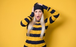 Panicking young woman stare to you, model wearing woolen cap and sweater, isolated on yellow background. Mistake. Bad news. Studio shot