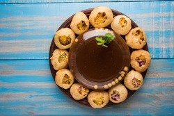Panipuri or Golgappa is a common street snack from India. It's a round, hollow puri filled with a mixture of flavoured water and other chat items. Over colourful or wooden background. Selective focus
