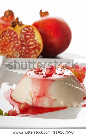 Panna cotta dessert  on white plate decorated with pomegrantes and mint