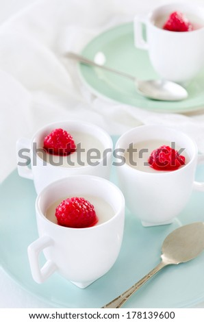 Panna cotta in cups topped with stewed raspberry, sweet italian dessert