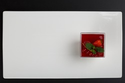 Panna cotta. Milk panna cotta with forest fruits. Panna cotta with different flavors, chocolate, smoothies, almond flakes. Panna cotta on a flat plate, on a white background.
