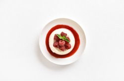 Panna cotta with fresh raspberries in bowl on white stone background with free space. Delicious healthy dessert. Top view, flat lay
