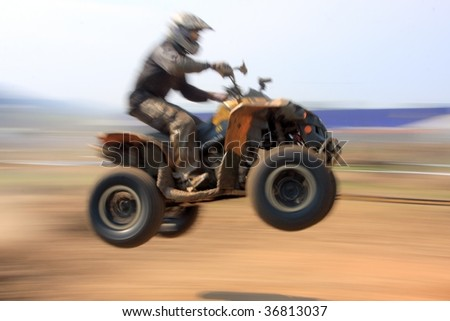 panned image of a motorbiker in the air - stock photo