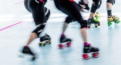 Panning action shot of skaters in a roller derby. Pan with motion blur.