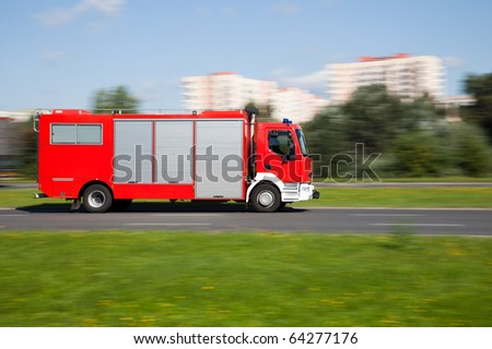 Panning image of a fire truck rushing on the street in intentional motion blur