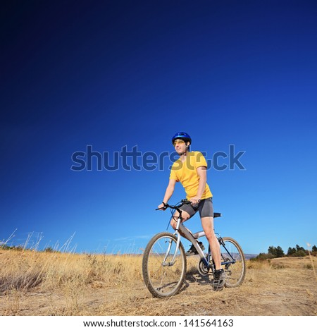 Panning shot of a bicycle rider riding a mountain bike outdoors on a sunny day against a cloudless blue sky