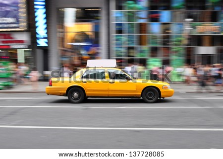 Panning shot of a NYC Taxi Cab at Times Square New York