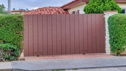 Pano Brown gate and white brick fence against red tile roof of house in San Diego CA. Palm trees, vines, and cloudy sky can also be seen in this residential view.